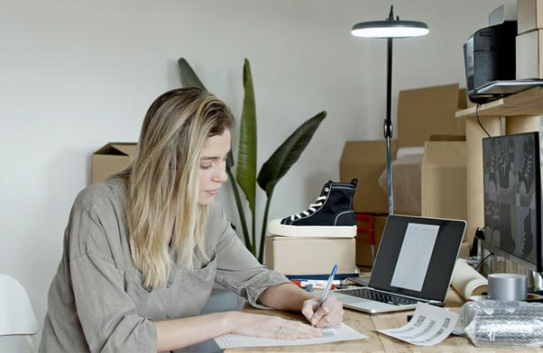 Woman writting at desk